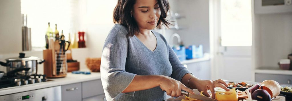Woman making a healthy meal in her kitchen.
